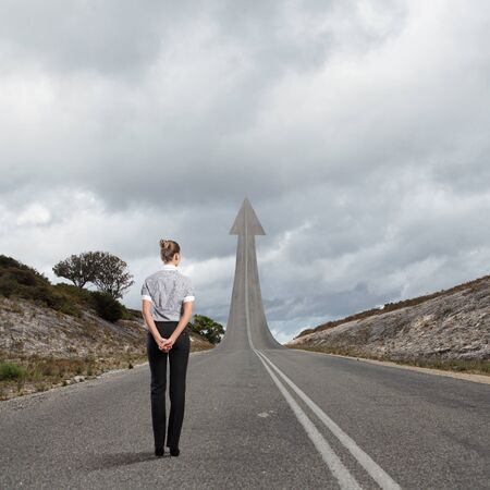 Concept of the road to success with a businesswoman standing on the road photo
