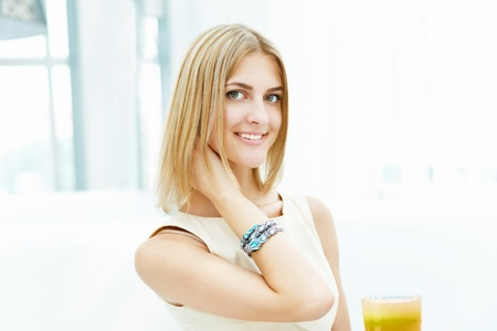 Portrait of a young blond woman sitting in cafe photo