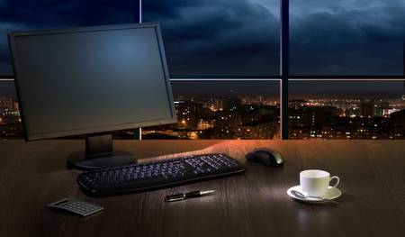 Work place in the office at night with a city view from window Stock Photo - 16982300