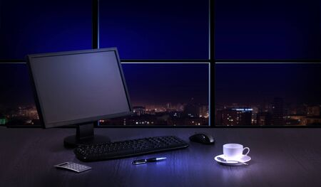 Work place in the office at night with a city view from window Stock Photo - 16982202