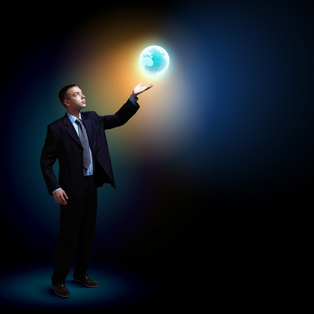 Young businessman standing with our planet Earth Stock Photo - 16982620