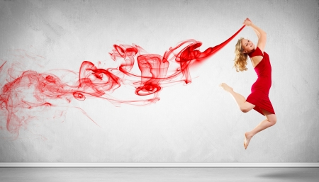 Portrait of a dancing young woman with red smoke photo