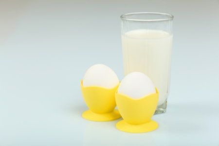 Milk in a glass jar and eggs on the table photo