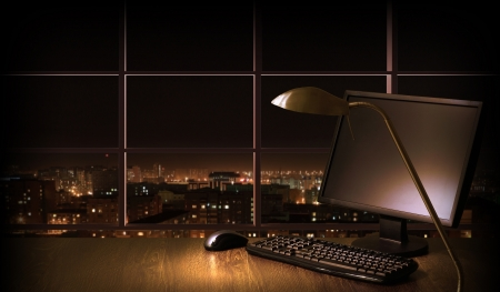Work place in the office at night with a city view from window Stock Photo - 16995858