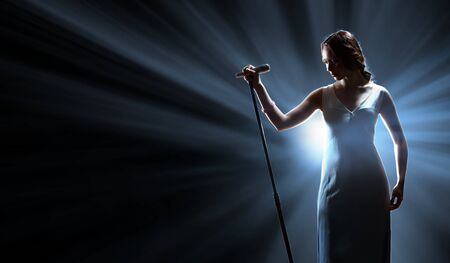 Female singer on the stage holding a microphone photo