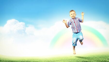 Photo of little boy jumping and raising hands photo
