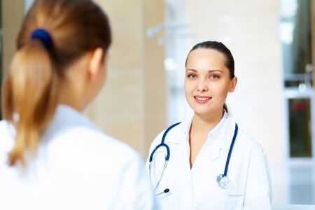 Portrait of two friendly female doctors in hospital discussing something photo