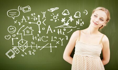 Portrait of young female teacher looking at camera by the blackboard photo