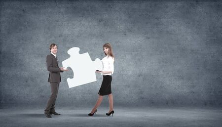 Team of business people collaborate holding up jigsaw puzzle pieces as a solution to a problem photo