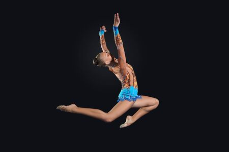 Young cute woman in gymnast suit show athletic skill on black background Stock Photo - 17022087