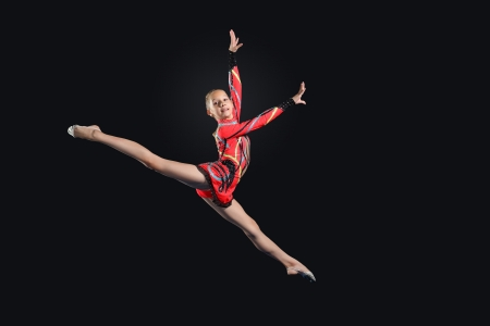 Young cute woman in gymnast suit show athletic skill on black background Stock Photo - 17022062
