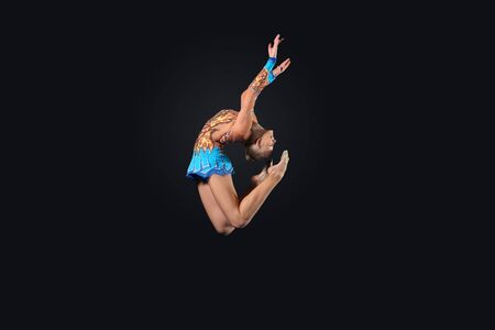 Young cute woman in gymnast suit show athletic skill on black background Stock Photo - 17022038