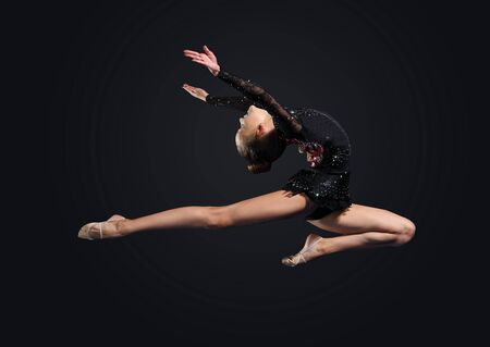 Young cute woman in gymnast suit show athletic skill on black background Stock Photo - 17022102