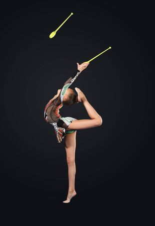Young cute woman in gymnast suit show athletic skill on black background Stock Photo - 17022012