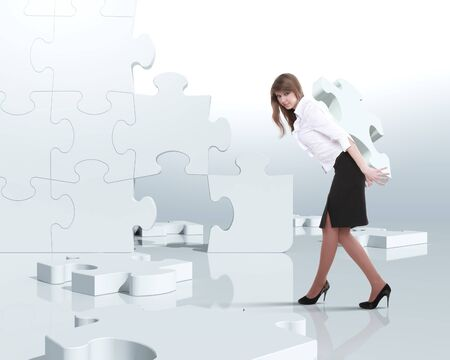 solves: Businesswoman with a puzzle pieces on the background Stock Photo