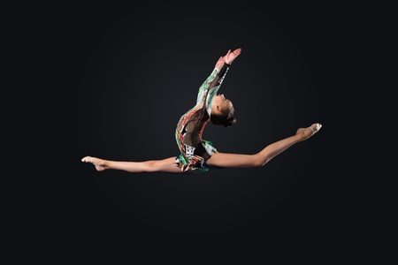 gymnastics: Young cute woman in gymnast suit show athletic skill on black background