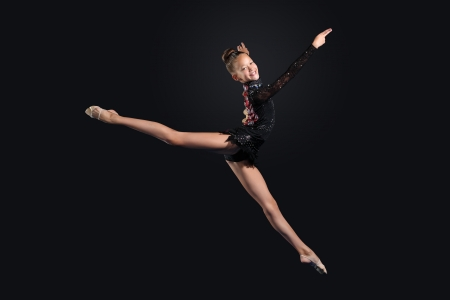Young cute woman in gymnast suit show athletic skill on black background Stock Photo - 17022000