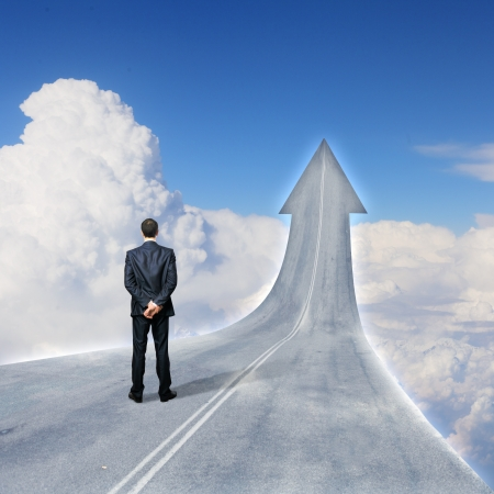 road ahead: Concept of the road to success with a businessman standing on the road