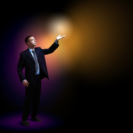 Young successful businessman holding a shining light in his hand as a symbol of success and advancement Stock Photo - 17022555