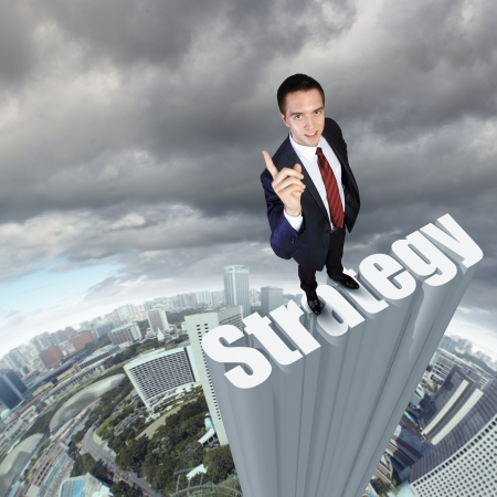 Businessman in suit standing on the word Strategy photo
