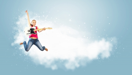 young woman playing on electro guitar and jumping photo