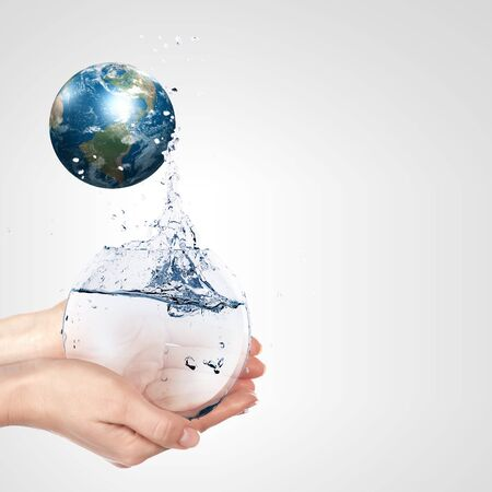water conservation: Globe in human hand against blue sky  Environmental protection concept  Elements of this image furnished by NASA