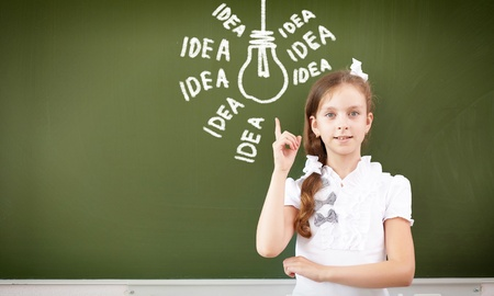 Scoolgirl standing in class near a green blackboard Stock Photo - 17056053