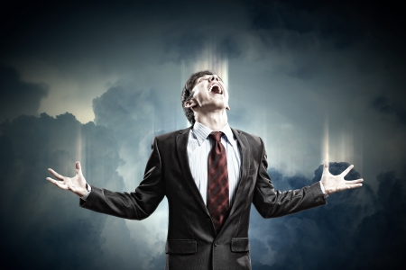 amok: businessman in anger screaming against cloudy background Stock Photo