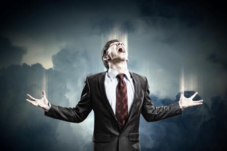 hombre de negocios con ira gritando contra el fondo nublado
