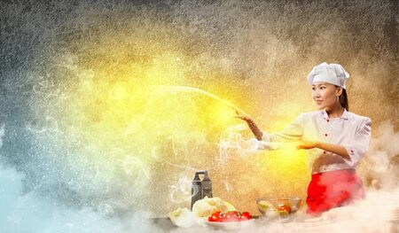 Asian female cooking with magic against color background Stock Photo - 17398826