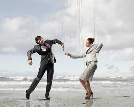 Image of businesspeople hanging on strings like manettes against sea background  Conceptual photography Stock Photo - 17398445