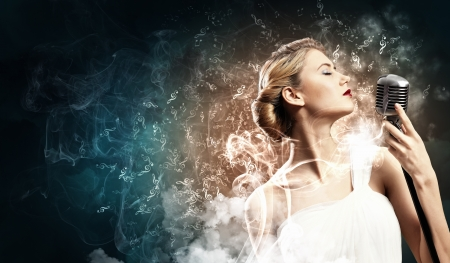 stage performer: Image of female blonde singer holding microphone against smoke background with closed eyes