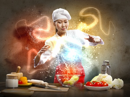 Asian female cooking with magic against color background Stock Photo - 17398659