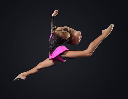 Young cute woman in gymnast suit show athletic skill on black background photo