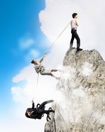 concentrating: Image of three businesspeople pulling rope atop of mountain Stock Photo