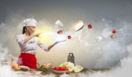 Asian female cooking with magic against color background Stock Photo - 17398052