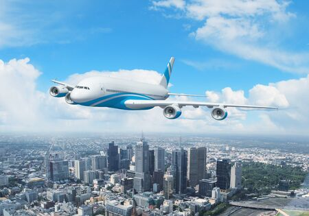 White passenger plane flying in the day blue sky above a city photo