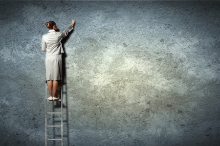 businesswoman standing on ladder drawing diagrams and graphs on wall Stock Photo - 17398815