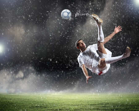 football players: jugador de f�tbol en la camisa blanca de golpear la pelota en el estadio bajo la lluvia