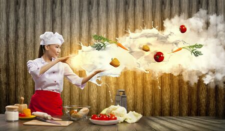 Asian female cooking with magic against color background Stock Photo - 17398593