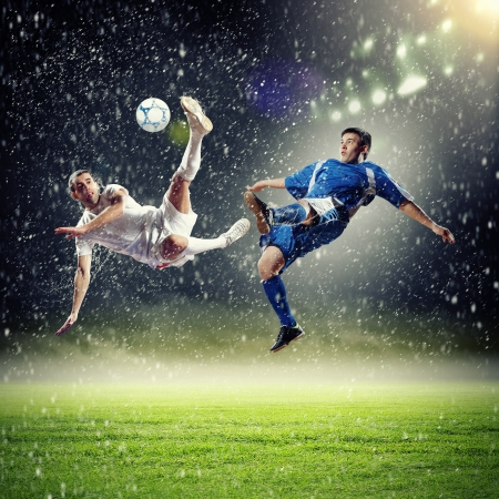 two football players in jump to strike the ball at the stadium under rain Stock Photo