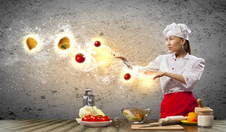 Asian female cooking with magic against color background Stock Photo - 17398584