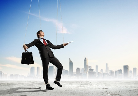 Image of businessman hanging on strings like marionette against city background  Conceptual photography photo