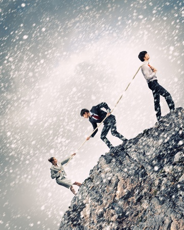 Image of three businesspeople pulling rope atop of mountain under falling snow photo