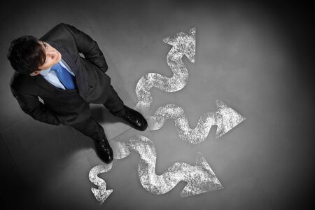 Top view of businessman standing against directions background Stock Photo - 17398551