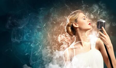 Image of female blonde singer holding microphone against smoke background with closed eyes photo
