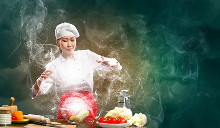 Asian female cooking with magic against color background Stock Photo - 17400166