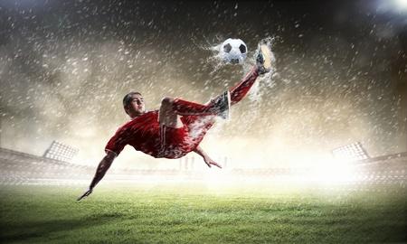 man field: football player in red shirt striking the ball at the stadium under rain