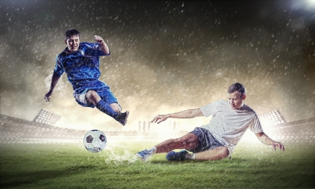 soccer match: two football players in jump to strike the ball at the stadium