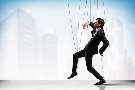 pull toy: Imagen de hombre de negocios que cuelgan en cadenas como marioneta en contra de fotograf�a conceptual fondo de la ciudad
